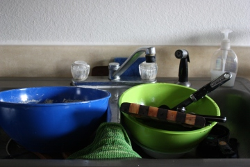 sink full of bowls, cutting boards, and other cooking utensils