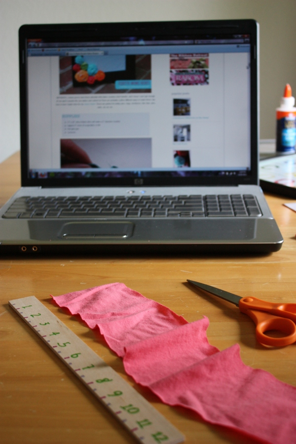 scissors, ruler, and jersey material in front of laptop showing rosette tutorial