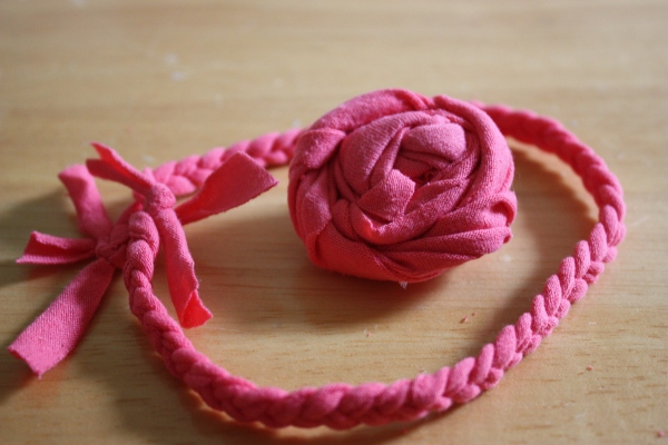 small braided circle of jersey material and rosette that's large in comparison