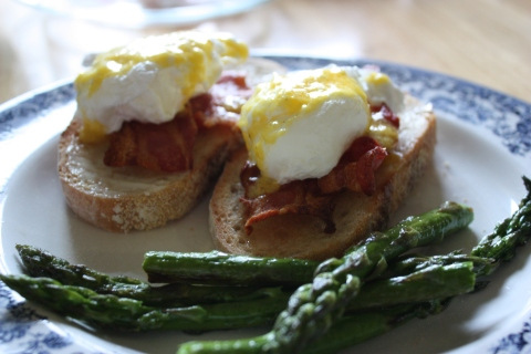 plate with two eggs Benedict and asparagus spears