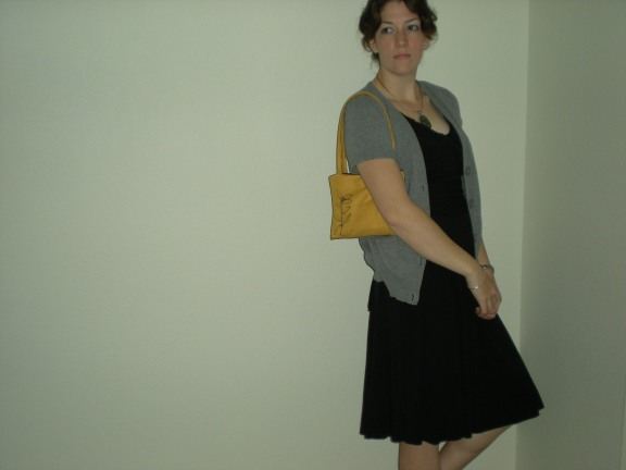 girl in black dress with gray sweater and yellow bag