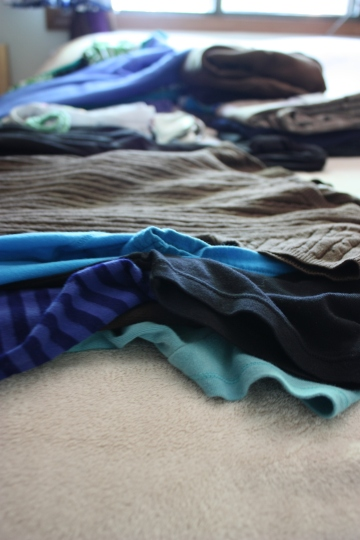 blue and green clothing on the bed