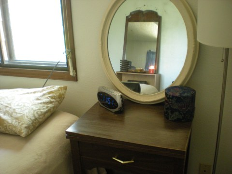 bedside table with alarm clock, mirror, fabric covered box