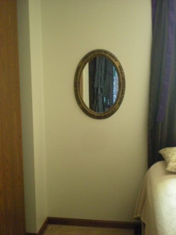 empty space by bed with mirror hanging on wall