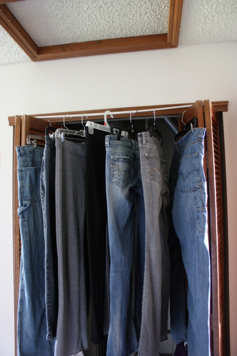 jeans hanging from a drying rod