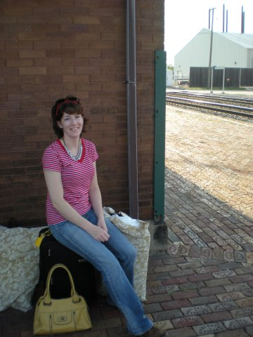 sitting on suitcase at train station