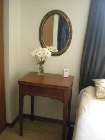 closer shot of sewing table by bedside with oval mirror and jar of daisies