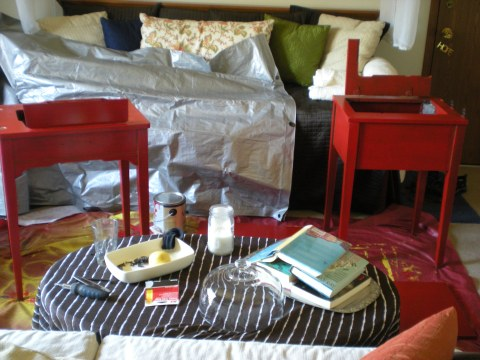 side tables painted red in a messy living room