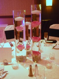 clear cylinders in three heights with floating pink roses and candles