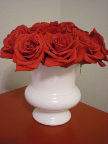 a dozen red roses in a white urn on a red tabletop