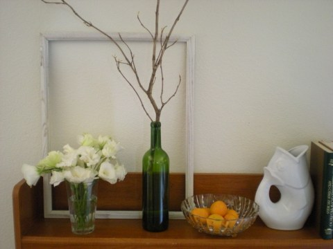 tableau with white lisianthus in a glass, white frame, green wine bottle with twigs, bowl of oranges, and white Gurgle pot