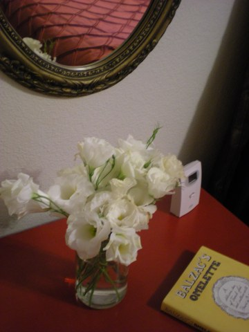 white lisianthus in a glass jar on a red tabletop with a yellow book