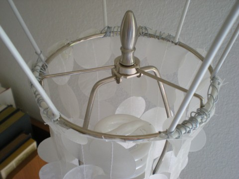 wire lampshade frame, upside down, anchored to lamp stand with finial