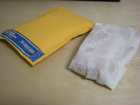 yellow envelope and paper towel-wrapped object