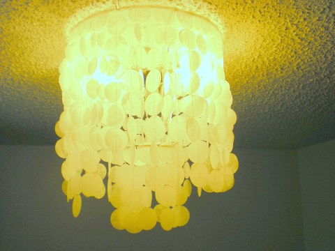 faux capiz chandelier hanging and lit