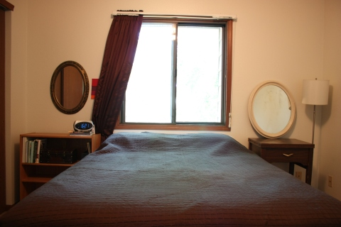 bedroom with brown curtain and bedspread, oval mirrors, brown bedside tables