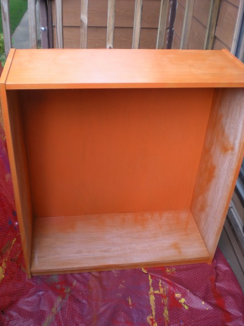 spray painting the shelf orange--on the balcony