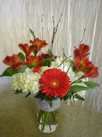 white hydrangea, red Gerbera daisies, red alstroemeria, and birch sticks in a bling cylinder vase
