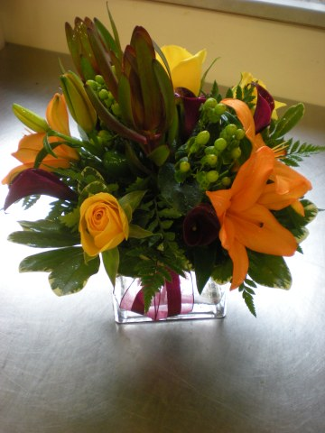 cube vase with orange lilies, yellow roses, leucadendron, green berries, and mini callas