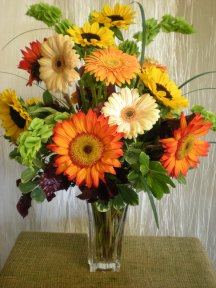 vase of sunflowers and Gerbera daisies with bells of Ireland