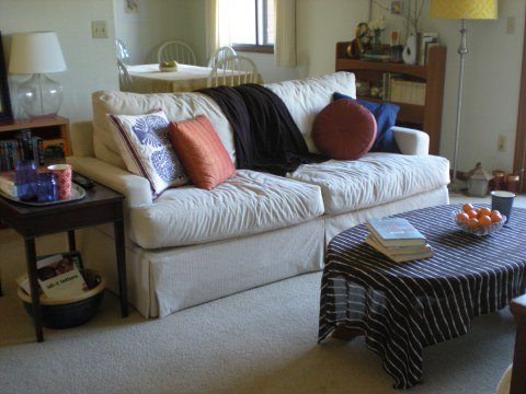 coffee table, couch, end table, bookshelf, with view into dining room