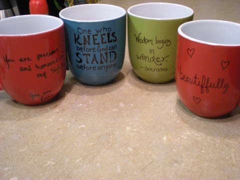 four mugs with Sharpied sayings on them