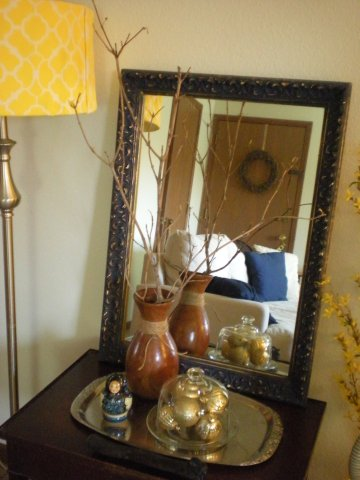 tableau with mirror, wooden vase & branches, silver platter, Russian doll, gold ornaments in cloche