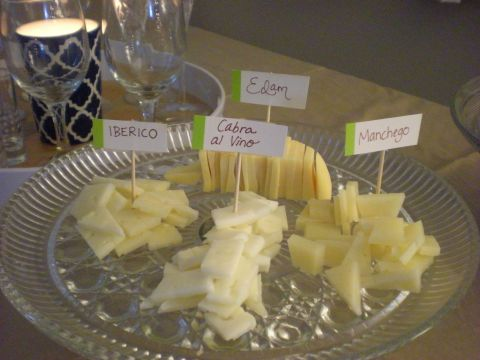 four cheeses, labeled with toothpicks on a cake stand