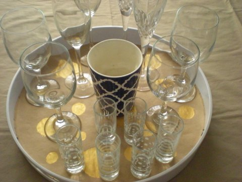 tray with brown paper, gold circles, wine glasses