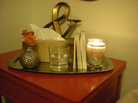 orange spray roses in a silver bud vase on the nightstand