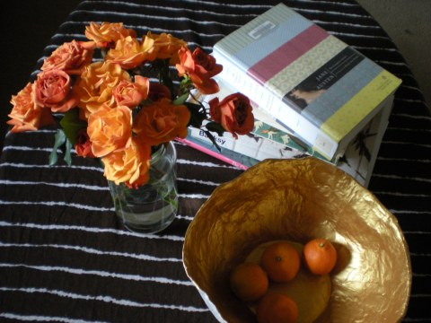 orange spray roses in a glass jar on the coffee table