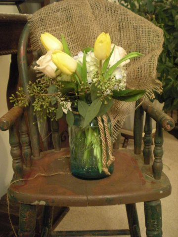 blue hydrangea, yellow tulips, seeded eucalyptus, and creme kiss roses in blue Mason jar on high chair