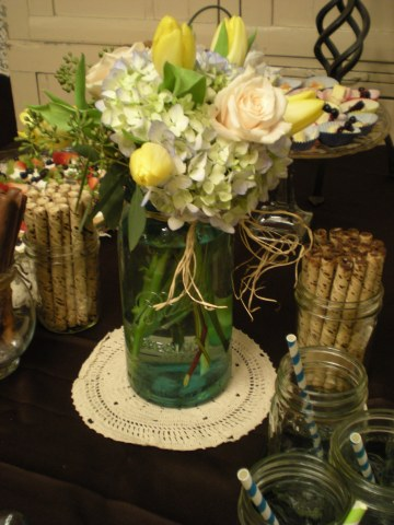 blue hydrangea, yellow tulips, seeded eucalyptus, and creme kiss roses in blue Mason jar on food table